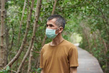 Concept of new normal. A senior Asian male wearing face mask while travelling at mangrove forest.