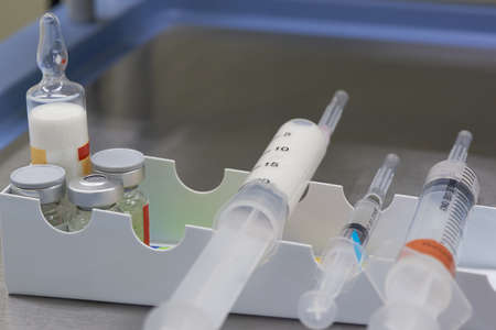 A white anesthetic drug in syringe and medications on the table in operating room 免版税图像