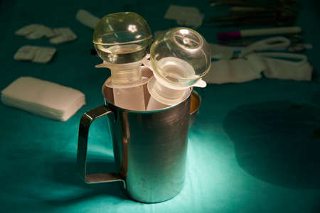 Irrigation bulbs in surgical cup and gauzes on operating room table