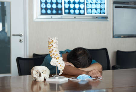 An Asian male neurosurgeon feels tired and sleeping in the medical office. Skull and lumbar spine model o the table, Brain MRI on board.
