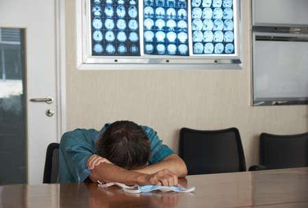 An Asian adult male feels tiredand sleeping in medical ofice. Brain MRI on board. Zdjęcie Seryjne