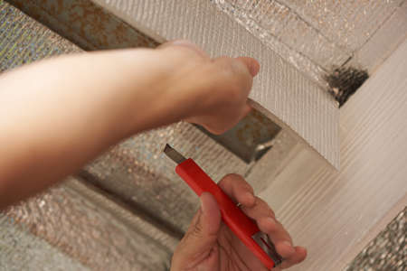 Hand holding cutter blade to cut silver reflective coated foam from the steel roof