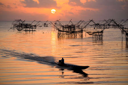 Phatthalung, Thailand-March  15,2021: Fisherman on long-tail boat and giant square fish net on background.