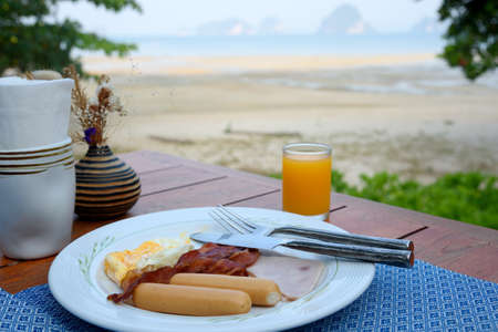 Delicious breakfast with cooked friedd egg, sausages, ham  and orange juice near the beach Stock fotó