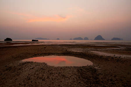 Beautiful twilight sky and orange clouds with reflection in water and mountain range at Tubkaak beach, Krabi province, Thailand