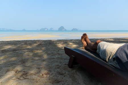 A man lying  on the beach chair at Tubkaak beach, Krabi province, Thailand.