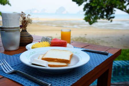 Delicious breakfast with bread and butter, fruits and orange juice near the beach. Background of Tubkaak beach, Krabi province, Thailand. Stock fotó