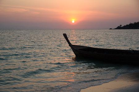 Scene of beautiful sunrise and silhouette of long tail boat at Lipe island, Satun province, Thailand. Stock fotó