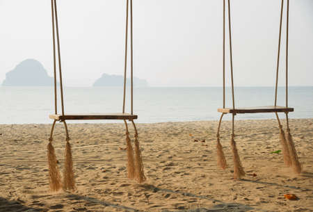 Two wooden swings in sunny day at Tubkaak beach ,Krabi province, Thailand.