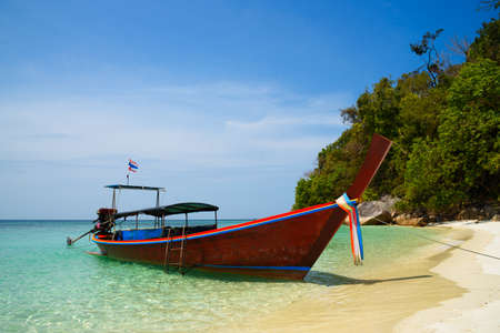 A longtail boat for tourists on the beautiful beach at koh Yang, Satun province, Thailand