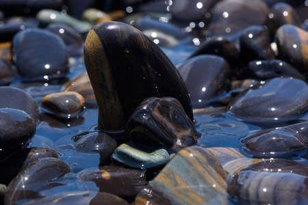 Close-up view of beautiful smooth black stones on the beach at koh hin ngam, Satun, Thailand. Stock fotó