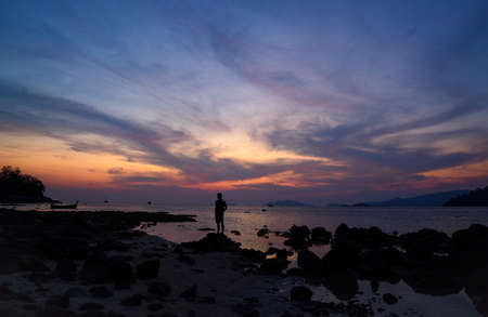 Scene of beautiful sunset at koh Lipe, Satun province and silhouette of a man on the beach