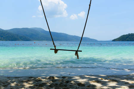 A wooden swing on the beach and turquoise sea in a sunny day