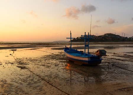 A longtail boat on the beach during low tide at Phuket province. Background of morning sunlight and beautiful sky. Stock fotó