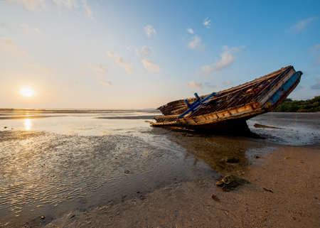 A shipwreck on the beach during low tide in the morning