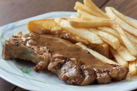 Close-up view of delicious porkchop, french fries and butter  on the plate