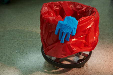 Used blue surgical glove on the red garbage bin in operating room