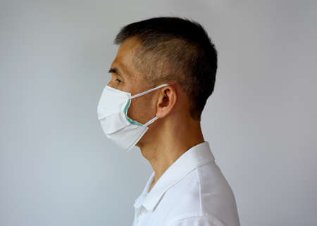 Asian senior adult man wearing double face mask, cloth mask and medical mask for highly covid-19 protection. Side view Stock Photo