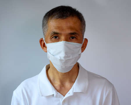 Asian senior adult man wearing double face mask, cloth mask and medical mask for highly covid-19 protection. Front view.