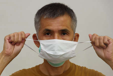 A senior adult asian man weraing cloth mask on medical face mask. Double face mask highly protect  pandemic delta variant.