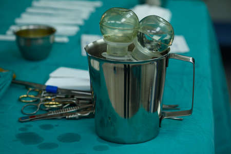 Irrigation bulb in silver container on green table. Surgical instruments in operating room. Stock Photo