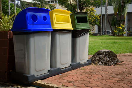 Garbage bins separated by colors foe recycling, glass and general waste placed outdoor.
