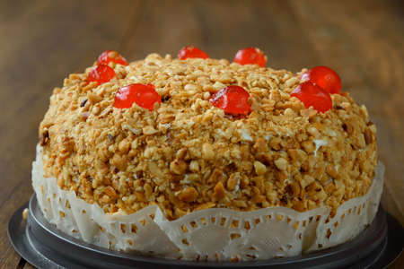 Close-up view of delicious cake with peanut and cherry ontop on wooden background. Stock Photo