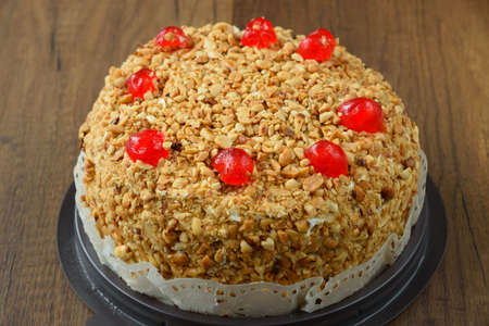 Delicious cake with peanut and cherry ontop on wooden background.
