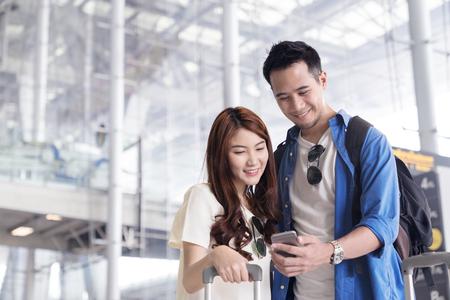 Para azjatyckich studentów podróżujących szuka lub znajduje do lotu w smartfonie na terminalu lotniska. Zameldowanie przez telefon komórkowy. Nastolatek jest pojęciem podróży.