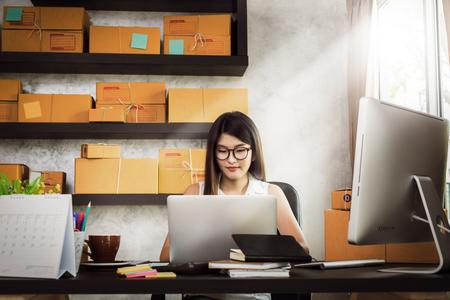 La bella donna asiatica affascinante di affari del proprietario dell'adolescente lavora a casa per lo shopping online, la scrittura dell'ordine e la preparazione del prodotto del pacchetto con attrezzature per ufficio, concetto di stile di vita dell'imprenditore
