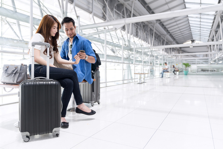 Young happy teenage asian couple check in by mobile and waiting in airport terminal. Couple sitting and using smartphone together, Air travel or holiday vacation concept.
