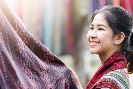 Happy asian traditional woman looking at Thai traditional fabric for dress making. Banco de Imagens