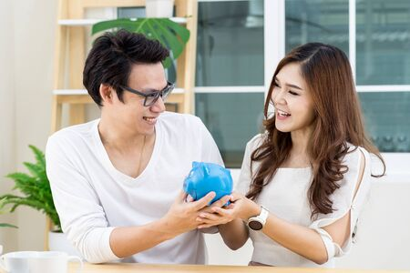 Young happy asian couple smile ,looking each other and holding piggy bank. Saving and happy family concept. Stock Photo