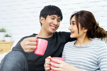 Happy Asian couple is smiling and looking each other at sofa in morning. Love and happiness concept.