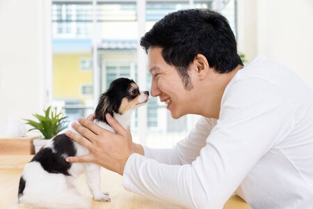 Happy asian man and tiny dog on the table at home. Human and Pet love each other. Feeling lovely and funny.