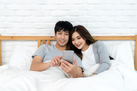 Young asian couple using smartphone for looking honeymoon trip, shopping gift valentines day or surfing the internet on the bed at bedroom sweet home. Love and happy holidays concept. Banco de Imagens