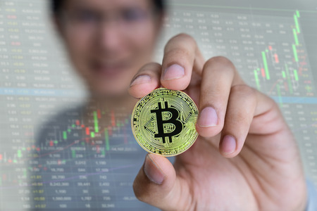 Close up Golden bitcoin in hands man with up trend stock market chart background. Man is showing BTC. Banco de Imagens