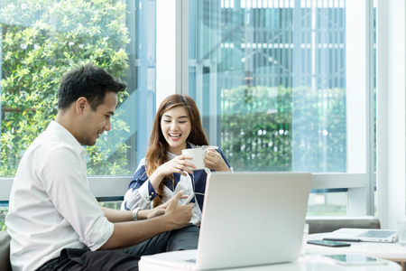 Young asian woman or officer woman having fun with partner using smartphone and talking. Young asian couple surf the internet with smartphone for finding data information or shopping online. Stock Photo