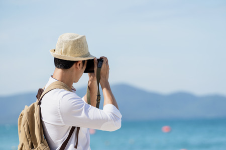 Young asian man take a photo pose. Man travel at sea and beach. Happy holidays concept. Foto de archivo