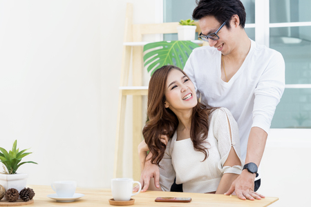 Young asian couple smiling and looking each other at home. Happy holiday at home. Love and happy concept.