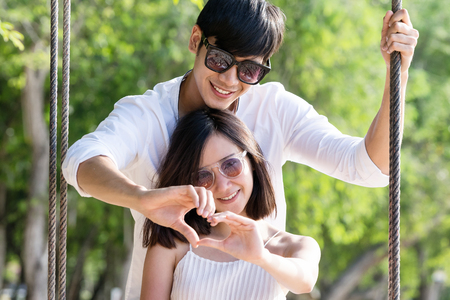 Portrait of happy asian couple in love with heart sign by their hands sunny day. Love and romance concept. Stock Photo
