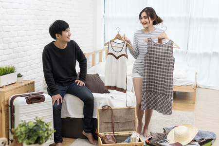 Asian couple looking, choose and prepare dress for travel or honeymoon. Woman show two dress by her hand. Man looking and smiling action. Love and travel concept. Foto de archivo