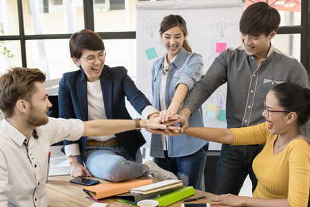 Group of Diverse happy business team in casual style Hands Together Joining.Office Team,Business Partner , Teamwork Togetherness Collaboration successful Concept. Stock Photo