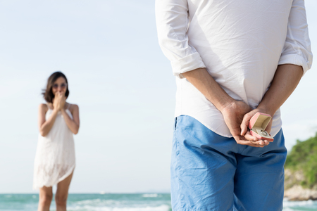 Asian young man is hiding marry ring for girlfriend behind him back while asian woman is standing on the beach. Stock Photo