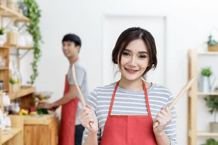 Portrait of smiling young asian woman is ready to cooking pose with smiling boyfriend background in kitchen at home. Asian couple in lovely home. Love in kitchen concept. Banco de Imagens