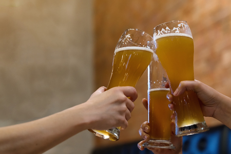 Group of friends enjoying a beer. Young people hands toasting and cheering beers pint - Friendship and hangout concept Foto de archivo