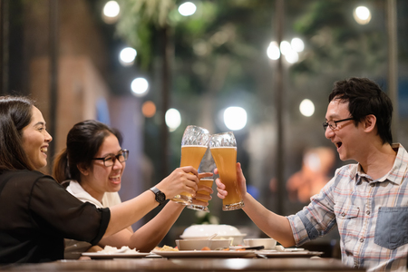 Group of asian friends are clinking or toasting with glasses of light beer at the restaurant. Young people hands toasting and cheering aperitif beers half pint. friendship and celebration concept. Foto de archivo