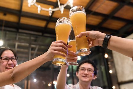 Group of asian friends are clinking or toasting with glasses of light beer at the restaurant. Young people hands toasting and cheering aperitif beers half pint. friendship and celebration concept. Stock Photo
