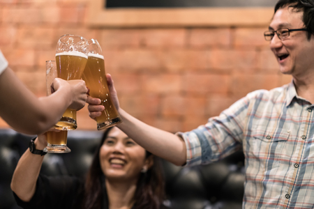 Group of happy asian friends cheering, clinking or toasting beer glasses at restaurant pub or bar. Happy male friends drinking beer and clinking glasses. friendship, drinking, cheers concept.
