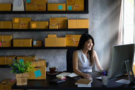 Young asian woman entrepreneur, teenager is work at home business owner by computer in morning. Happy woman is smilling for her work. SME work at home concept.